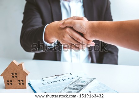 Sale Agent handshake with woman customer and sign agreement documents for realty purchase after successful loan contract #1519163432