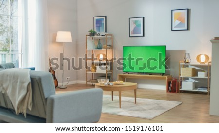 Cozy Living Room with Stylish Furniture and Design, Green Chroma Key TV in the Middle of the Room. #1519176101