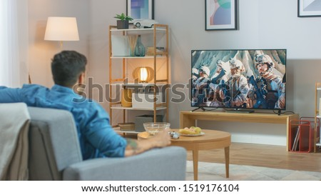 In the Living Room: Guy Relaxing on a Couch Watching War Movie on a TV. Modern Military Warfare Action with War Soldiers Shown on a Television. #1519176104