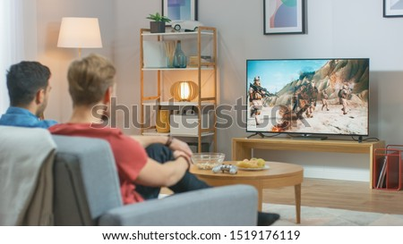 In the Living Room: Two Friends Relaxing on a Couch Watching War Movie on a TV. Modern Military Warfare Action with Shooting and Explosions Shown on a Television. Royalty-Free Stock Photo #1519176119