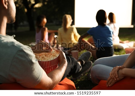 Young people with popcorn watching movie in open air cinema, closeup. Space for text Royalty-Free Stock Photo #1519235597
