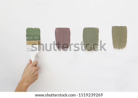 A different color swatches on the white wall. Process of choosing the right color for the wall, DIY home improvement concept.