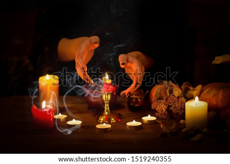 Witch guessing on wax on the altar in the dark. Female hands with sharp black nails making passes above candles, pumpkin, nuts, dry leaves, magic herbs, selected focus, low key. Halloween, Yule #1519240355