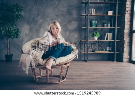 Full size photo of focused middle aged blonde hair woman use her cellphone read social media network enjoy autumn holidays sit on furniture white armchair covered with checkered blanket in  room indoo