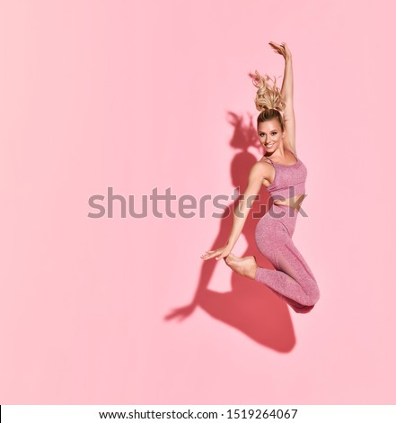 Happy athletic woman jumping in silhouette. Photo of sporty woman in fashionable pink sportswear on pink background. Sport and healthy lifestyle. Dynamic movement. #1519264067