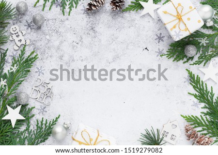 Christmas frame composition with thuja branches, white stars, pine cones, wrapped gifts amd festive ornaments against concrete background. Overhead view, flat lay with copy space #1519279082