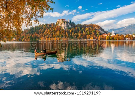 Romantic couple is sailing by boat on Bled lake. Castle rock with medieval fortress, colorful hills under beautiful sky reflected in lake water. Bled lake is best travel destination in Slovenia #1519291199