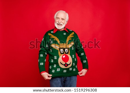 Look I got wonderful present! Portrait of positive cheerful funky old man show his theme christmas party sweater deer decor design wife gift have newyear celebration isolated red color background #1519296308