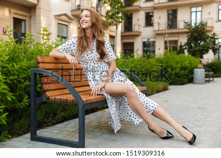 Image of a happy pleased cheery positive young redhead woman sit on a bench outdoors at the street in dress. #1519309316