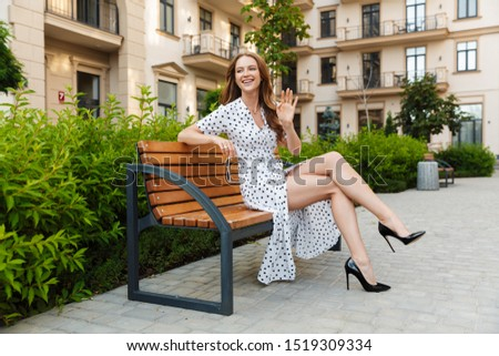 Photo of happy cheery pretty young redhead woman sit on a bench outdoors at the street in dress waving to friends. #1519309334