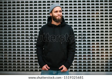 City portrait of handsome hipster guy with beard wearing black blank hoodie or sweatshirt and hat with space for your logo or design. Mockup for print #1519325681