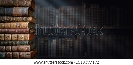 Old books on wooden shelf and ray of light. Bookshelf history theme grunge background. Concept on the theme of history, nostalgia, old age. Retro style. Royalty-Free Stock Photo #1519397192