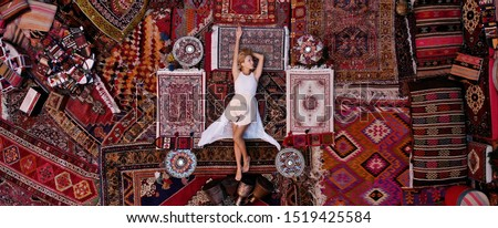 Beautiful happy girl in a long white dress laying on the carpet and rugs in Goreme, Cappadocia, Turkey. Top view drone. #1519425584