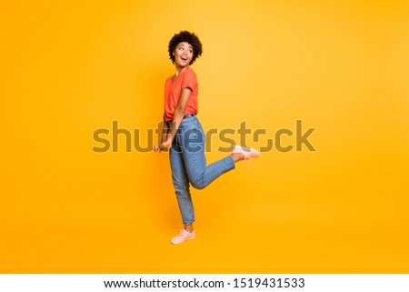 Full length body size photo of cheerful cute sweet girlfriend hesitating to look at what interested her wearing jeans denim orange t-shirt footwear isolated over yellow vivid color background #1519431533