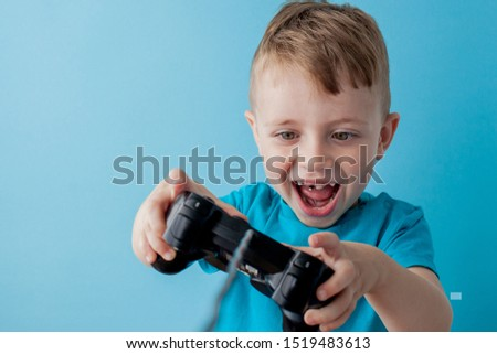 Little kid boy 2-3 years old wearing blue clothes hold in hand joystick for gameson blue background children studio portrait. People childhood lifestyle concept. Mock up copy space. #1519483613