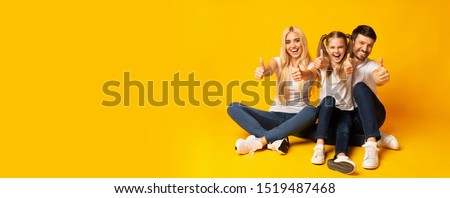 Like. Excited Family Gesturing Thumbs Up Looking At Camera Sitting On Floor Over Yellow Background. Studio Shot