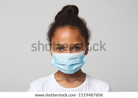 Infection concept. Portrait of little african american girl wearing medical mask, grey background #1519487606