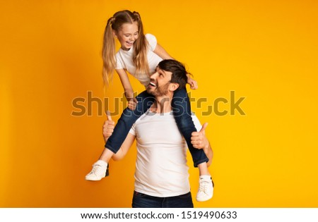 Best Father. Happy Daughter Sitting On Dad's Shoulders Gesturing Thumbs-Up On Yellow Studio Background. Empty Space #1519490633