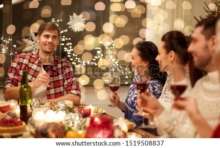 holidays and celebration concept - happy friends with glasses of wine having christmas dinner and speaking toast at home #1519508837