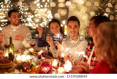 winter holidays and people concept - happy friends with sparklers celebrating christmas at home feast #1519508849
