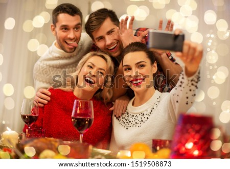 holidays and celebration concept - happy friends taking selfie by smartphone at home christmas dinner