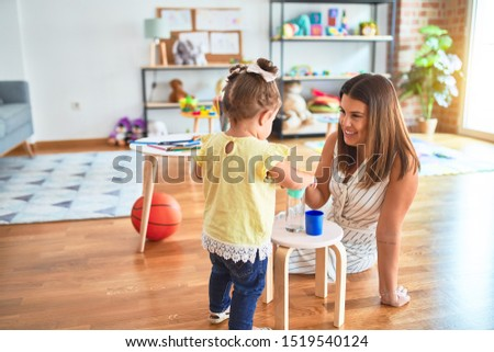 Young beautiful teacher and toddler playing with plastic cups toy at kindergarten #1519540124