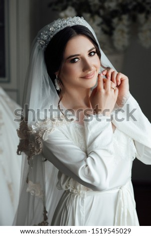 Preparing the bride for the upcoming wedding. Beautiful bride dresses earrings. Beautiful bride with stylish make up and hair style. Sexy bride. Bride's preparation at home before the wedding ceremony #1519545029