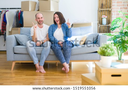 Young couple sitting on the sofa arround cardboard boxes moving to a new house pointing finger up with successful idea. Exited and happy. Number one. #1519551056