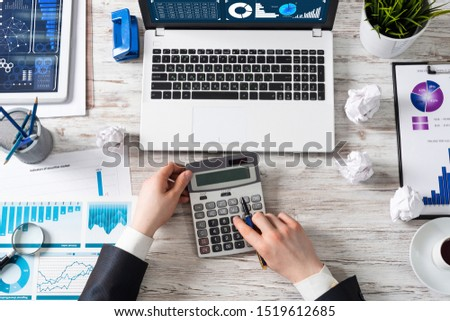 Businessman working at office desk with financial analytics. Top view office workplace with human hands calculating data. Flat lay table with laptop, calculator, business charts and cup of coffee. #1519612685