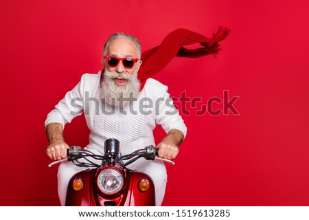 Portrait of elderly modern person in eyewear eyeglasses driving his bike wearing white sweater isolated over red background #1519613285