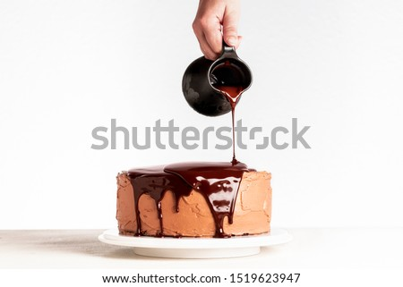 Glazing chocolate cake with melted chocolate. Woman pouring chocolate over cake. Homemade cocoa layered cake. Birthday cake and dripping chocolate. #1519623947