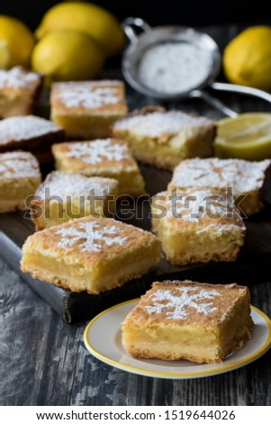 A small plate with a lemon dessert square with a platter board of several lemon squares in behind. #1519644026