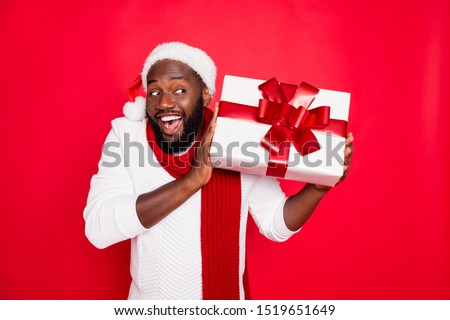 Portrait of amazed funky dark skin man wear santa claus headwear hold big package receive on x-mas  time celebration scream wow feel interested wear style pullover isolated over red color background #1519651649