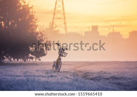 Morning foggy bike before sunrise. The outlines of houses in the fog. A lone bicycle stands on a path in the fog. Off-road before dawn in the fog. Silhouettes of urban buildings. #1519665410
