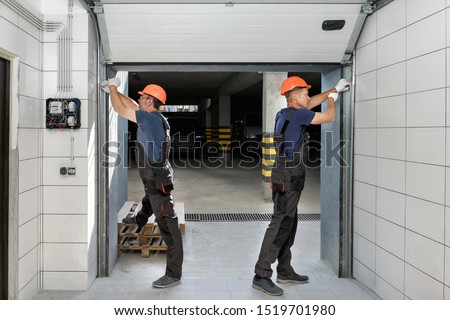 Workers are installing lifting gates of the garage. Royalty-Free Stock Photo #1519701980