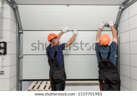 Workers are installing lifting gates of the garage. Royalty-Free Stock Photo #1519701983