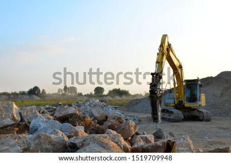 Crawler excavator with hydraulic breaker hammer for the destruction of concrete and hard rock at the construction site or quarry.  Jackhammer using without blasting method. Hard rock demolition  Royalty-Free Stock Photo #1519709948