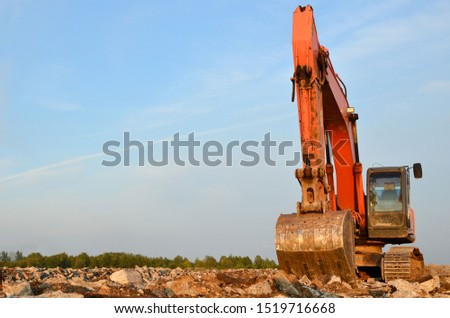 Excavator with a large iron bucket breaks asphalt on a construction site. Demolition work concrete, replacing asphalt, road works. Stone mine in open pit. Loading of stone and rubble  #1519716668