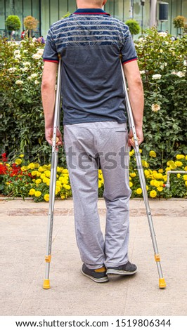 Man with crutches walks in the park. #1519806344