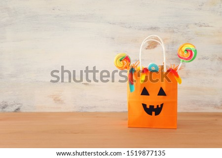 holidays image of Halloween. Pumpkins, bats, treats, paper gift bag over wooden table