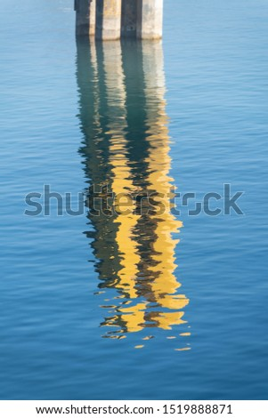 Bollard in the harbor reflecting on the water surface in the sunlight