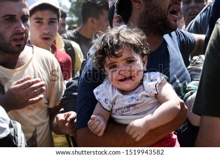 Idomeni, Greece - August 29, 2015. A Syrian refugee girl cries in his father's arms as refugees wait to cross the Greek Macedonian border. #1519943582