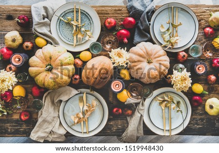 Fall table setting for Thanksgiving day party or family gathering dinner. Flat-lay of plates, silverware, floral and fruit decoration, candle and pumpkins over rustic wooden table background, top view #1519948430