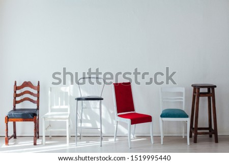 many different chairs of different colors stand at the white wall #1519995440