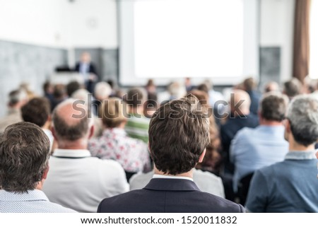 Speaker giving a talk in conference hall at business event. Audience at the conference hall. Business and Entrepreneurship concept. Focus on unrecognizable people in audience. #1520011832