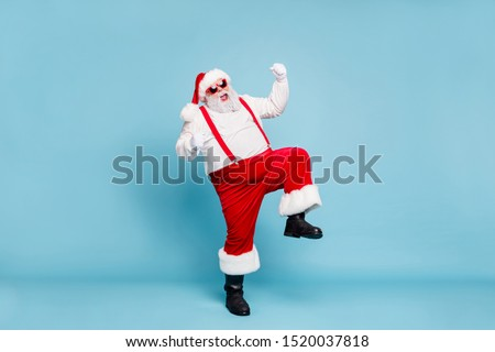 Full body photo of crazy funny funky fat santa with big belly raise fists scream yeah enjoy christmas party wear red pants style stylish boots overalls spectacles isolated over blue color background #1520037818