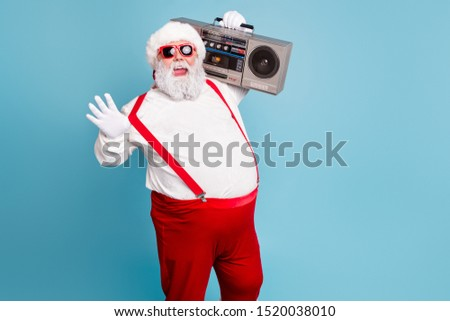 Portrait of nice bearded cheerful funky funny glad big belly Santa carrying tape player having fun isolated over bright vivid shine vibrant blue turquoise color background #1520038010