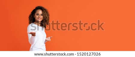 Happy smiling young African American woman doing welcome or presenting gesture with open hands isolated on orange banner background with copy space
