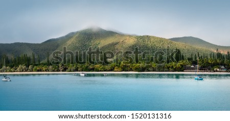 Kuto Bay Panorama with tropical vegetation, white beach with a waterfront restaurant and Pic N'Ga Mountain top engulfed in clouds and sun-lit mountain ridges on Isle of Pines, New Caledonia.
