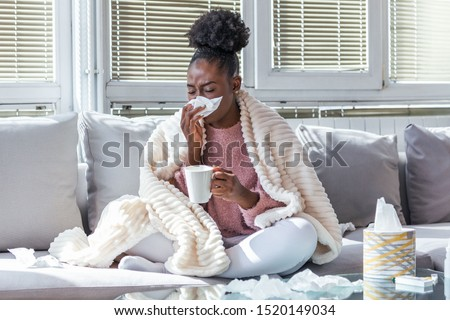 Sick day at home. African American woman has runny nose and common cold. Cough. Closeup Of Beautiful Young Woman Caught Cold Or Flu Illness. Portrait Of Unhealthy Girl Drinking Tea. Royalty-Free Stock Photo #1520149034